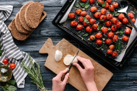 Woman cutting mozzarella cheese for sandwiches with herbs and baked tomatoes on dark wooden table