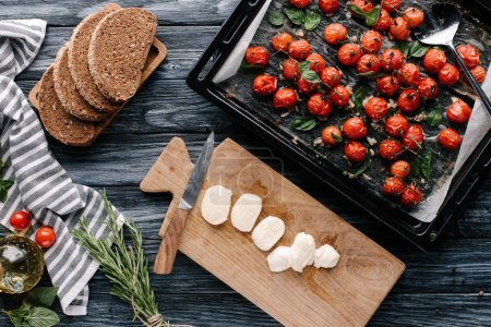 Pieces of bread and mozzarella on dark wooden table with tomatoes in baking pan