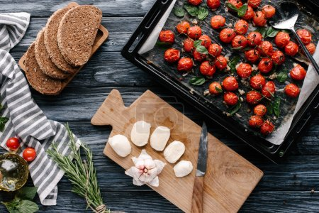 Pan with baked tomatoes on dark wooden table with bread and cheese