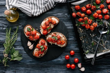 Delicious sandwiches with mozzarella and baked tomatoes on dark slate board