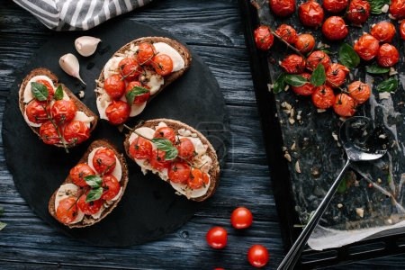 Bread sandwiches with cheese and baked tomatoes on dark wooden table