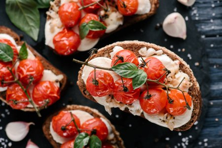 Photo for Delicious sandwiches with mozzarella and baked tomatoes on dark wooden table - Royalty Free Image