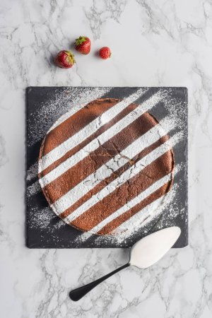 tasty homemade brown cake with icing on slate board and fresh strawberries on marble surface