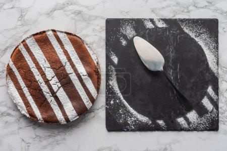 top view of delicious homemade cake and spoon with frosting on slate board