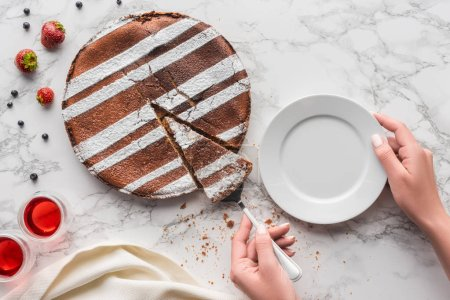 partial top view of person putting piece of delicious homemade cake on plate