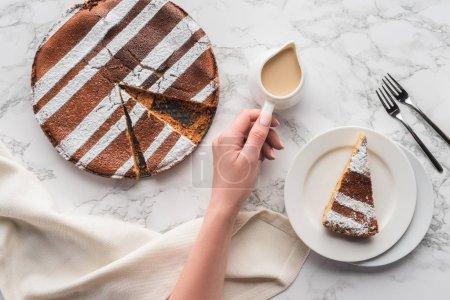 abgeschnittene Aufnahme einer Person mit Krug mit heißer Schokolade und köstlichem hausgemachtem Kuchen auf Marmoroberfläche