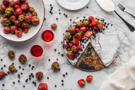 top view of delicious homemade cake, fresh berries and summer drink on marble surface