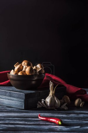 Photo for Close up view of bowl with champignons, garlic and chili pepper on wooden table on black - Royalty Free Image