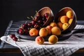 close up view of bowls with cherries and apricots on tray on wooden table