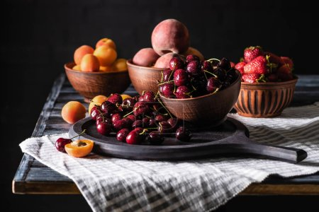 selective focus of bowls with cherries, strawberries, peaches and apricots on wooden table on black