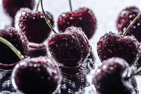 close up view of red ripe cherries with water drops on wet surface