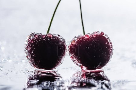 selective focus of red ripe cherries with water drops on wet surface