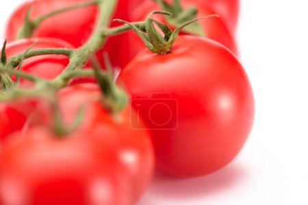 selective focus of fresh cherry tomatoes on twig on white background