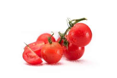 close up view of fresh cherry tomatoes on twig isolated on white