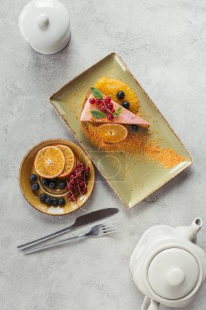 flat lay with piece of sweet carrot cake with berry filling, teapot and cutlery on grey tabletop