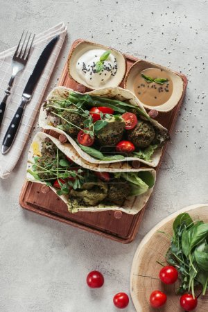 Photo for Top view of falafel with tortillas, cherry tomatoes and germinated seeds of sunflower served on wooden board on grey surface - Royalty Free Image