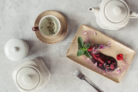 food composition with piece of blueberry cake served with mint leaves and violet petals on plate, teapot and cup of herbal tea on grey tabletop