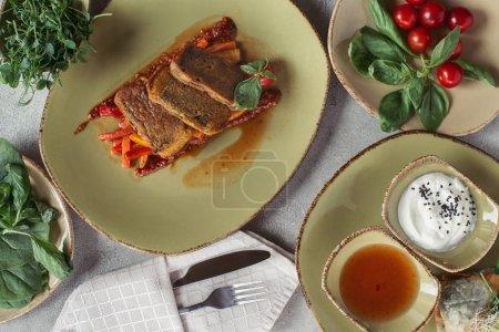 flat lay with fresh vegetables, paneer in nori seaweed on vegetable julienne and cutlery on grey tabletop