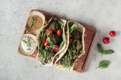 top view of falafel with tortillas, cherry tomatoes and germinated seeds of sunflower served on wooden board on grey surface