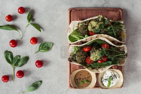 Photo for Flat lay with falafel with tortillas, cherry tomatoes and germinated seeds of sunflower served on wooden board on grey surface - Royalty Free Image