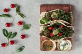 flat lay with falafel with tortillas, cherry tomatoes and germinated seeds of sunflower served on wooden board on grey surface