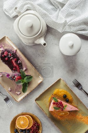 Photo for Flat lay with sweet carrot cake with berry filling, blueberry cake served with mint leaves and violet petals, teapot and linen on grey tabletop - Royalty Free Image