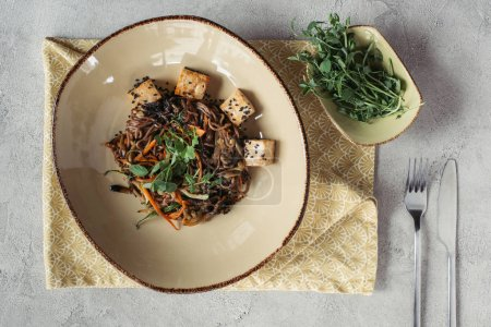 food composition with sprouts in bowl, soba with tofu and vegetables decorated with germinated seeds of sunflower on grey tabletop