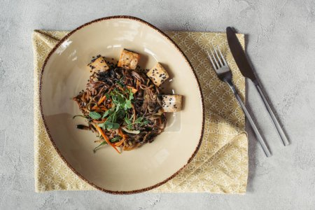 food composition with soba with tofu and vegetables decorated with germinated seeds of sunflower on grey tabletop