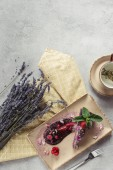 food composition with piece of blueberry cake served with mint leaves and violet petals on plate, lavender and cup of herbal tea on grey tabletop
