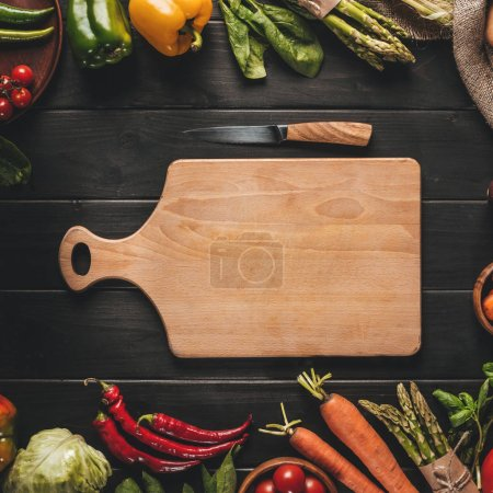 top view of wooden cutting board with knife and organic fresh vegetables around on black wooden tabletop