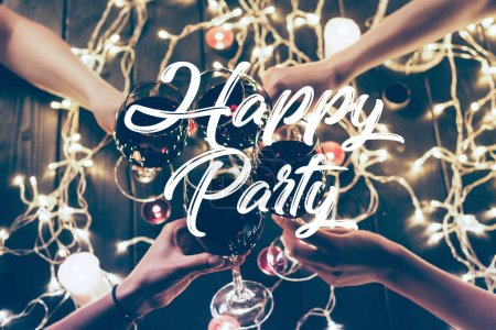 Photo for Cropped shot of four people clinking glasses with red wine over wooden table with fairylights decorations, happy party inscription - Royalty Free Image