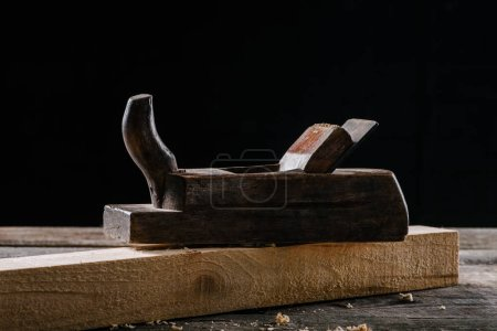 close up view of vintage woodworker plane and plank isolated on black