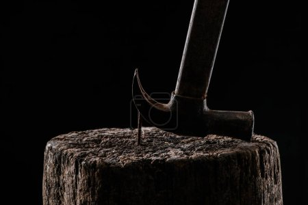 close up view of vintage rusty hammer and nail in wooden stump isolated on black