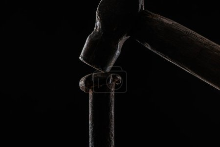 close up view of vintage hammer and nail isolated on black