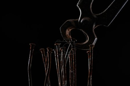 close up view of vintage rusty pliers and nails isolated on black