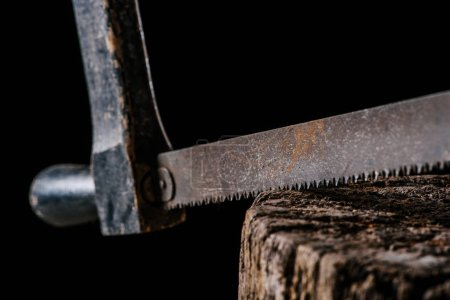 close up view of vintage saw on wooden stump isolated on black