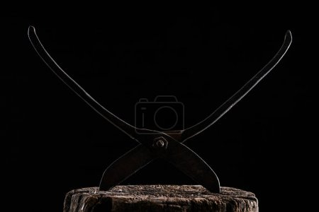 close up view of retro rusty scissors on wooden stump isolated on black