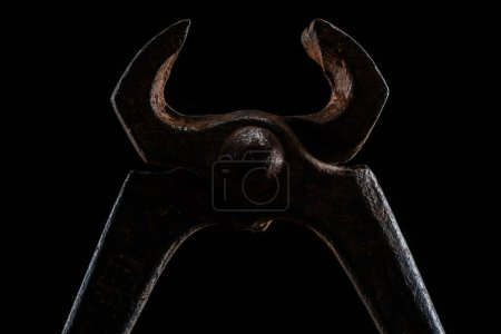 close up view of vintage rusty pliers isolated on black