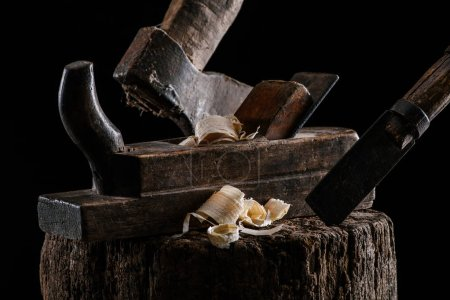 close up view of woodworker plane, axe and chisel carpentry tools on stump isolated on black
