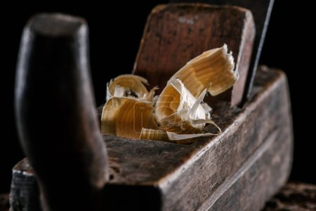 selective focus of vintage woodworker plane and wooden chips isolated on black