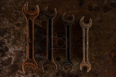 Photo for Top view of arrangement of vintage wrenches on rusty surface - Royalty Free Image