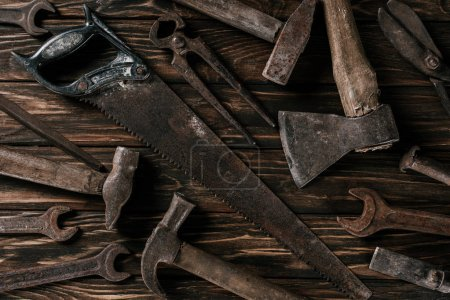 Photo for Flat lay with assortment of vintage rusty tools on wooden surface - Royalty Free Image