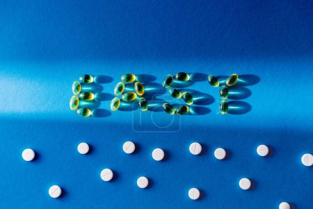 top view of lettering easy by pills near white tablets on blue background with sunlight