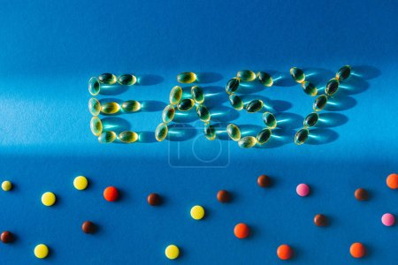 top view of lettering easy by pills near various tablets on blue background with sunlight