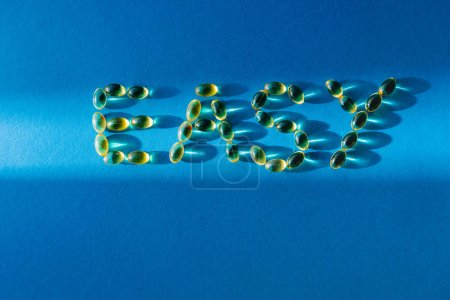 top view of lettering easy by pills on blue background with sunlight
