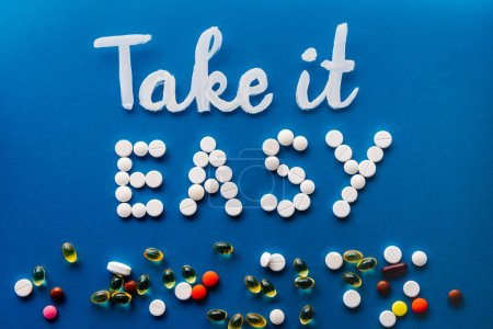 top view of lettering take it easy made by white pills near various tablets on blue background