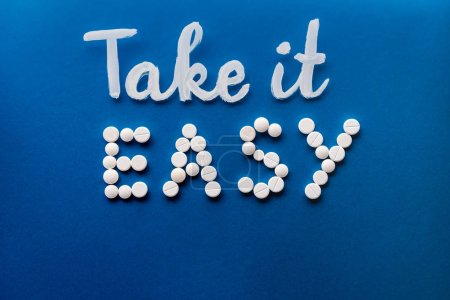 Photo for Top view of lettering take it easy made by white pills on blue background - Royalty Free Image
