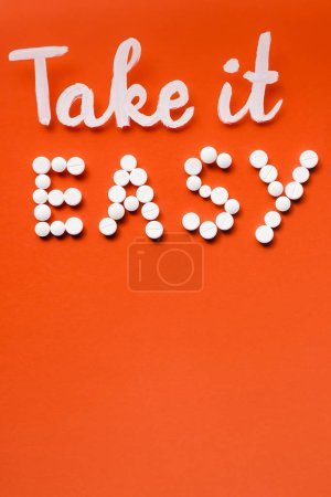 top view of lettering take it easy made by white pills on red background
