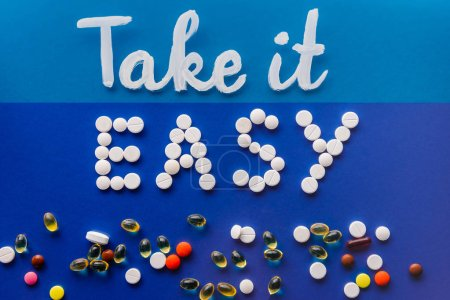 top view of lettering take it easy by white pills near various tablets on blue background