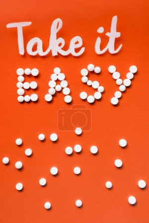 top view of lettering take it easy by white pills on red background